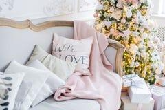 Stack pläd och kuddar på en soffa hemma på en julhelgdagsafton Hem- cosiness royaltyfri foto