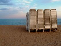 Stacked Sunbeds on the beach at dusk. A stack of plastic sunbeds on a deserted beach in Spain at the end of the day Royalty Free Stock Image