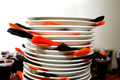 Stack of plates. Plates stacked ontop of each other with orange and black napkins Royalty Free Stock Image
