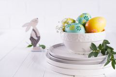 Stack of plates and bowl with colorful Easter eggs, spring. easter decoration on white. Wooden table royalty free stock photography