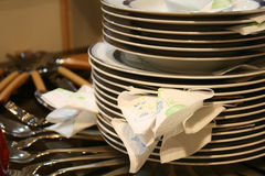 Stack of plates and utensils. Stack of plates and bowls on table, surrounded by utensils stock photo