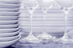 Stack of plates with wineglasses and more plates i Stock Photos