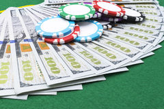 Stack of Poker chips on a dollar bills, Money. Poker table at the casino. Poker game concept. Playing a game with dice. Casino Stock Photography