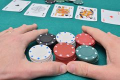 Stack of poker chips in two hands and cards on a gambling table. With chips stock photos