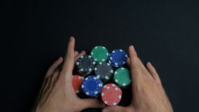 Stack of poker chips and two hands on table. Closeup of poker chips in stacks on green felt card table surface. Poker. Chips and hands above it on green table royalty free stock photos
