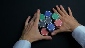 Stack of poker chips and two hands on table. Closeup of poker chips in stacks on green felt card table surface. Poker. Chips and hands above it on green table royalty free stock image