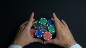 Stack of poker chips and two hands on table. Closeup of poker chips in stacks on green felt card table surface. Poker. Chips and hands above it on green table stock image