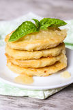 Stack of potato pancakes or fritters with apple sauce and fresh basil leaves on a plate Stock Photo