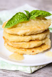 Stack of potato pancakes or fritters with apple sauce and fresh basil leaves on a plate Stock Image