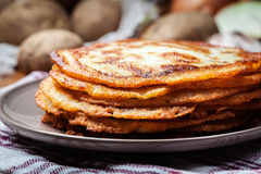Stack of potato pancakes on a wooden table. In the background potatoes Stock Image