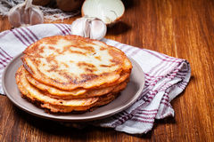 Stack of potato pancakes on a wooden table. In the background potatoes Stock Photography