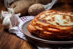 Stack of potato pancakes on a wooden table. In the background potatoes Royalty Free Stock Photography