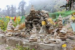 Stack of prayer stones in pyramid form symbolizing zen, harmony and balance commonly found around Bhutan Dzong. Stack of prayer stones in pyramid form Stock Photo