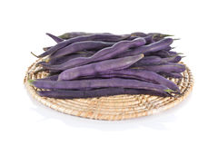 Stack of purple beans on rattan tray and white background Stock Photography