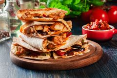 Stack of quesadillas with chicken, sausage chorizo and red peppe. R served with salsa. Mexican cuisine. Side view Stock Photos
