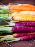 Stack of rainbow carrots with neatly trimmed tops sorted by color in close up stock photo