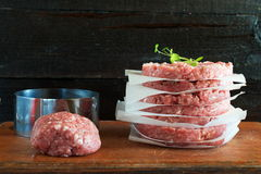 Stack of raw homemade beef burgers on a wooden cutting board with some minced meat and metal form on a background. Home healthy ea Royalty Free Stock Photos