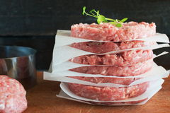 Stack of raw homemade beef burgers on a wooden cutting board with some minced meat and metal form on a background. Home healthy ea Royalty Free Stock Photography