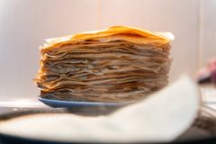 A stack of ready-made fried pancakes. pancakes are fried on a black frying pan royalty free stock photos