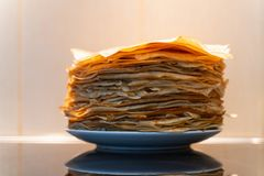 A stack of ready-made fried pancakes. pancakes are fried on a black frying pan royalty free stock images