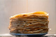 A stack of ready-made fried pancakes. pancakes are fried on a black frying pan stock images