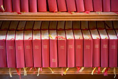 Stack of red bible books in church. Sweden, Europe Royalty Free Stock Photography
