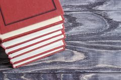 A stack of red books on a wooden table. concept of reading habit royalty free stock photo