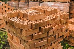 Stack of red brick for construction. Common quality building bricks stacked ready for use. stock photos