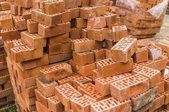 Stack of red brick for construction. Common quality building bricks stacked ready for use. royalty free stock images