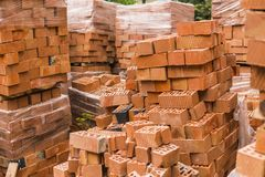 Stack of red brick for construction. Common quality building bricks stacked ready for use. royalty free stock photos