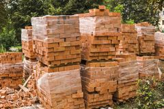Stack of red brick for construction. Common quality building bricks stacked ready for use. royalty free stock image
