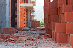 Stack of red building blocks on messy site Stock Image