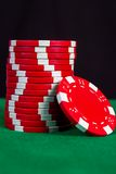 Stack of red chips on a green playing table Stock Image