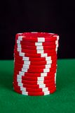 Stack of red chips on a green playing table Royalty Free Stock Photography