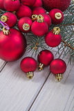 Stack of red christmas balls on branch of pinetree and white boa Royalty Free Stock Images