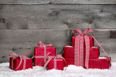 Stack of red Christmas gifts,snow on grey wooden background. Grey wooden background as a voucher with red giftboxes for christmas with snow Royalty Free Stock Photo