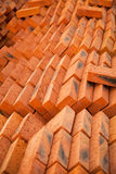 Stack of red new bricks nicely arranged at the construction site. Orange pattern background Stock Photos