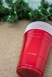 Stack of red party cups on a burlap background with Christmas garland. Concept for a Christmas party where alcohol is. Served royalty free stock photo