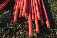 Stack red plastic electricity cable protection pipes royalty free stock photos