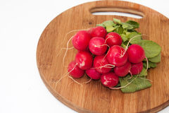 Stack of red radish on wooden board.  Royalty Free Stock Images