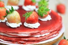 Stack of red velvet crepe cake with fresh strawberries.  stock image