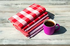 Stack of red white checkered and striped linen tableclothes and. A cup of coffee on rustic bright wooden table. Outdoor Stock Photo