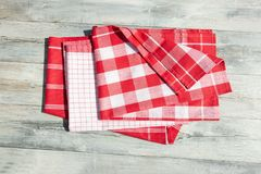 Stack of red white checkered and striped linen tableclothes on r. Ustic bright wooden table. Outdoor Stock Photography