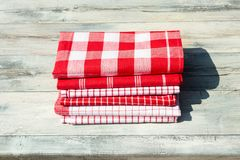 Stack of red white checkered and striped tableclothes on rustic. Bright wooden table. Outdoor Royalty Free Stock Image