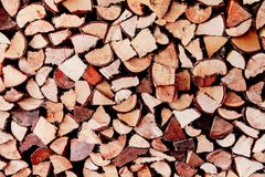 Stack of reddish natural firewood in preparation for the winter and used for camp fires, fireplaces and home heating. Chopped and piled wood background texture Stock Images