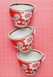 Stack of retro cups with red patterns on a tablecloth whith polka dots. Stack of retro cups with red patterns on a tablecloth whith polka dots stock photography