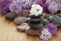 Stack of rocks. Pile of rocks with flowers on a bamboo mat. Focus on white flower on top of stack Stock Photography