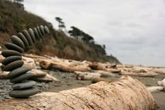 Falling rock stack on beach. Stack of rocks caught mid-fall on driftwood log at beach stock photography