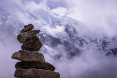 Stack of rocks in front of alpine background. Cusco, Peru in October 2015: A stack of rocks in front of a snow topped mountain. Pile of rocks are often used as Royalty Free Stock Images