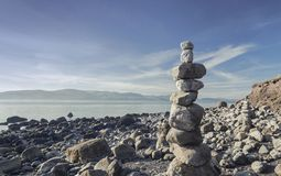 Stack of Rocks on menai Strait Shore. Stack of rocks on  Menai Strait with spectacular view over Snowdonia hills. Anglesey Island in North Wales. UK Stock Photography